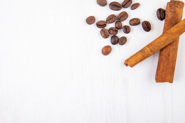 Vista superior de granos de café tostados y palitos de canela sobre fondo blanco de madera con espacio de copia