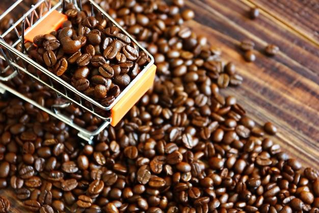Vista superior de granos de café tostados en un pequeño carrito de compras en granos de café en el espacio de copia de piso de madera retro
