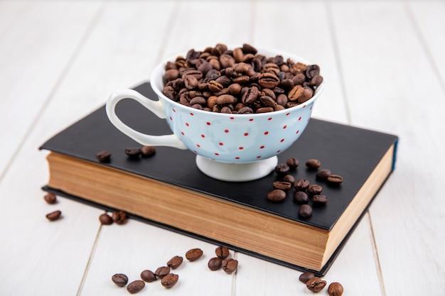 Vista superior de los granos de café tostados en una taza de lunares sobre un fondo de madera blanca