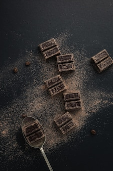 Vista superior de granos de café y trozos de chocolate amargo espolvoreados con cacao en polvo