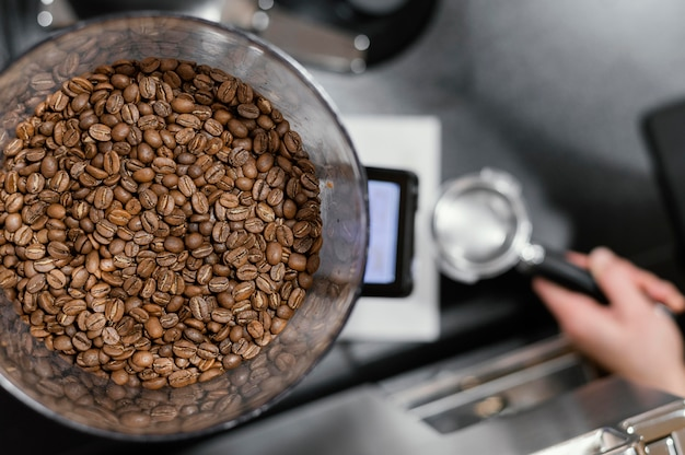 Vista superior de granos tostados de café y barista femenina preparando café