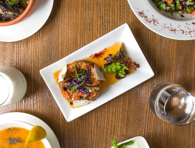 Vista superior gratinado de ternera en salsa de caldo con hierbas dentro de un plato blanco.