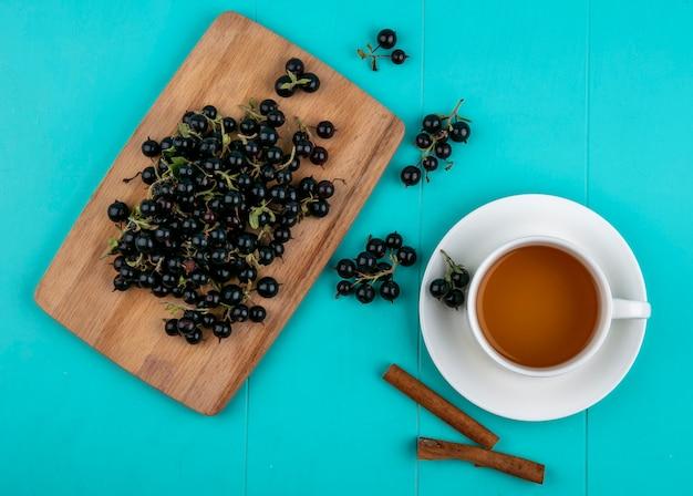 Vista superior de grosella negra en una pizarra con una taza de té y canela sobre un fondo azul claro