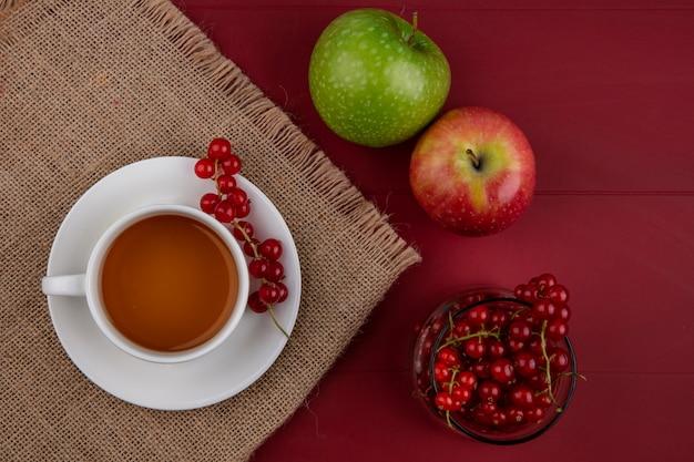 Vista superior de grosella roja en un vaso con una taza de té y manzanas sobre un fondo rojo.