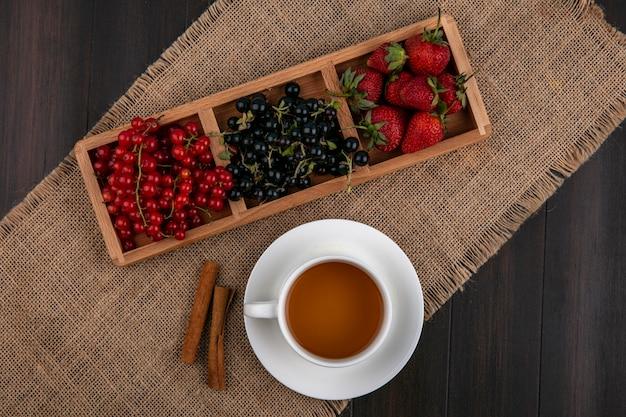 Vista superior grosellas rojas y negras con fresas y una taza de té con canela sobre un fondo de madera
