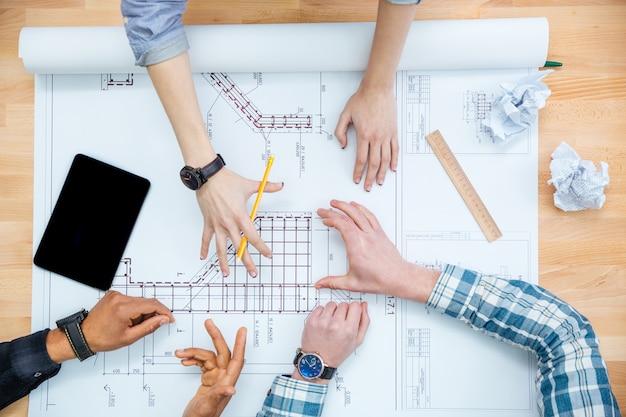 Vista superior del grupo de achetects dibujando planos juntos