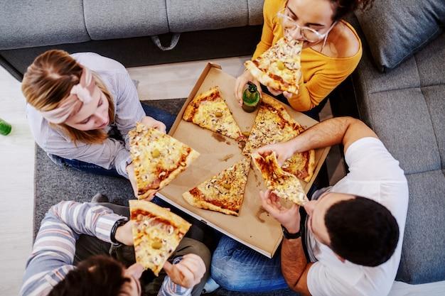 Vista superior del grupo de amigos sentados en el suelo de la sala de estar, bebiendo cerveza y comiendo pizza. fiesta en casa.