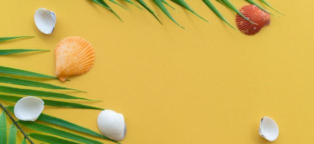 Vista superior del grupo de conchas de mar en amarillo pastel banner