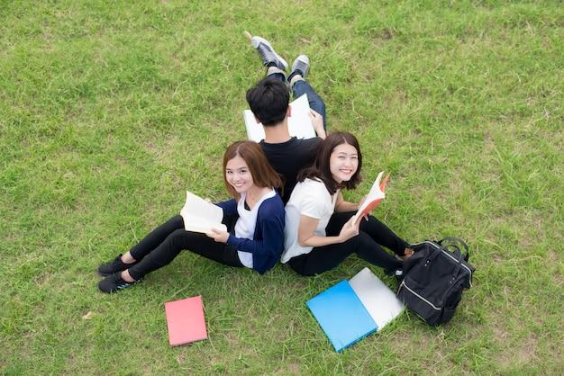 Vista superior del grupo de estudiantes asiáticos sentados juntos en el parque.