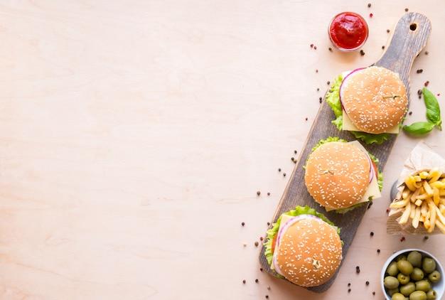 Vista superior grupo de hamburguesas con salsa y papas fritas