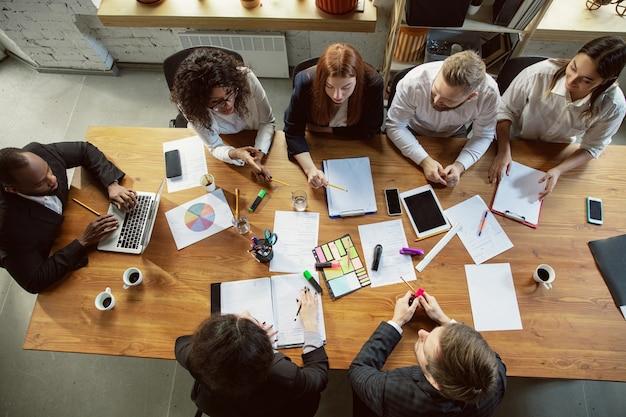 Vista superior. grupo de jóvenes empresarios que tienen una reunión. grupo diverso de compañeros de trabajo discuten nuevas decisiones, planes, resultados, estrategia. creatividad, lugar de trabajo, negocios, finanzas, trabajo en equipo.
