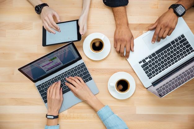Vista superior del grupo multiétnico de jóvenes usando computadoras portátiles y tabletas y tomando café