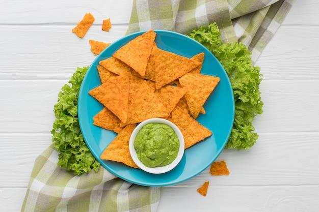 Vista superior guacamole fresco con nachos sobre la mesa