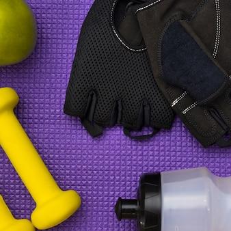 Vista superior de guantes de gimnasia con pesas y manzana