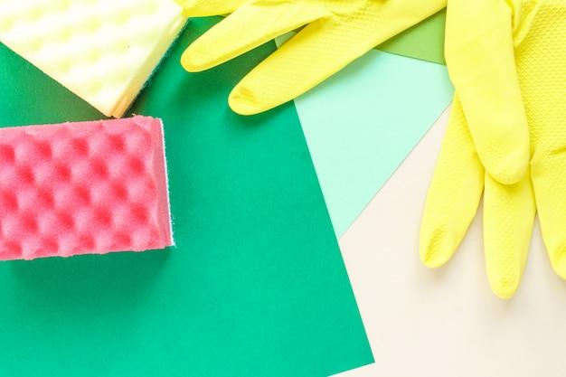 Vista superior de guantes de goma amarilla y dos esponjas sobre fondo brillante multicolor con espacio de copia