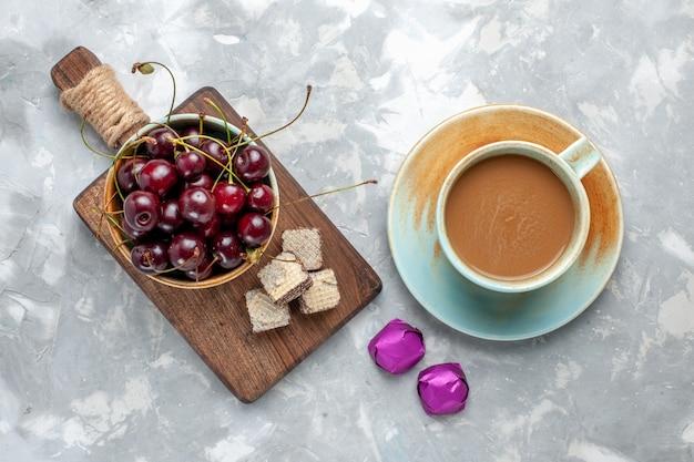 Vista superior de guindas con gofres y café con leche en el escritorio gris pastel de bebida de azúcar dulce de fruta