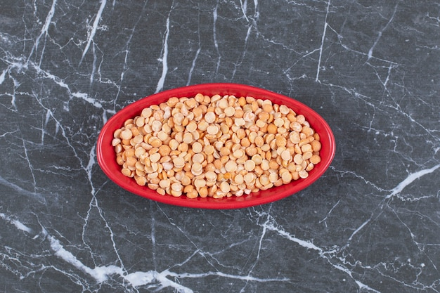 Vista superior de guisantes secos en un tazón rojo sobre piedra negra.