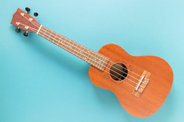 Vista superior guitarra acústica con fondo azul.