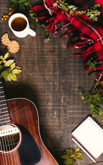 Vista superior guitarra acústica sobre fondo de madera con espacio de copia