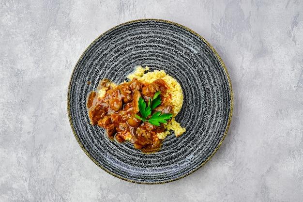 Vista superior de gulash de ternera con gachas de mijo y salsa cremosa