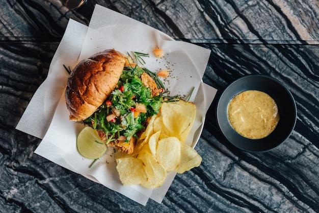 La vista superior de la hamburguesa asada de la ensalada de pollo sirvió con las patatas fritas y la salsa de mostaza en la tabla superior de mármol.