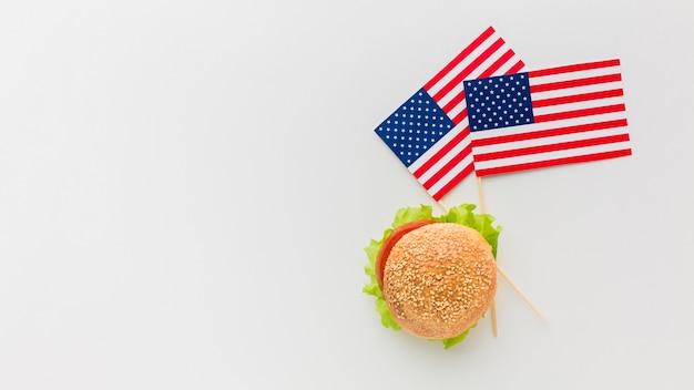 Vista superior de hamburguesa con banderas americanas y espacio de copia