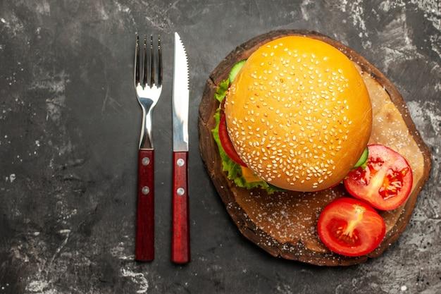 Vista superior de hamburguesa de carne con verduras y queso en un sándwich de comida rápida de bollo de piso oscuro