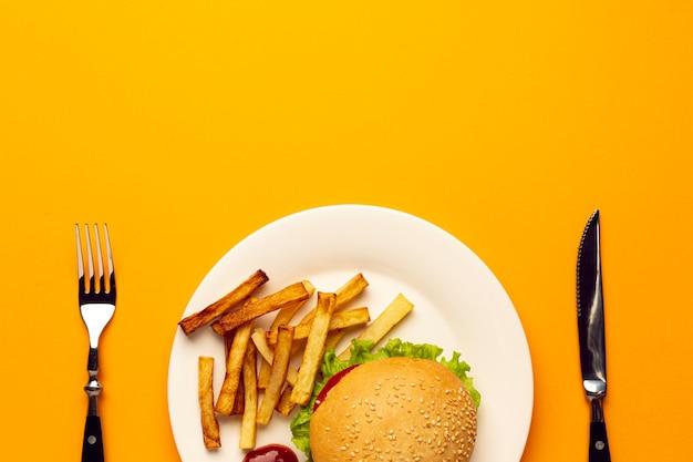 Vista superior hamburguesa y papas fritas en un plato
