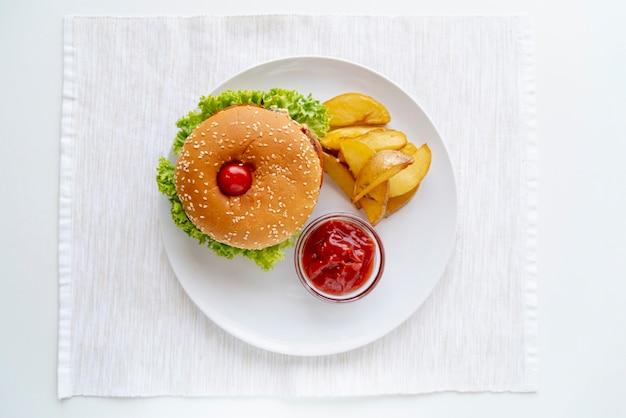 Vista superior hamburguesa con papas fritas en un plato