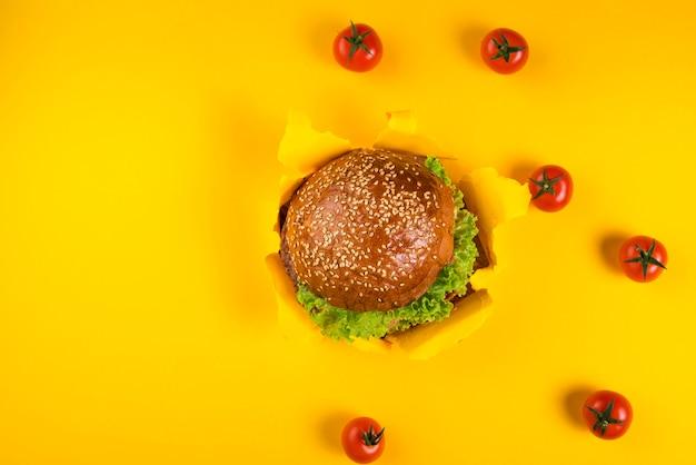 Vista superior hamburguesa de ternera rodeada de tomates cherry