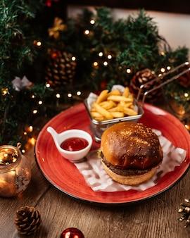 Vista superior de hamburguesa de ternera servida con papas fritas ketchup oreja decoraciones navideñas