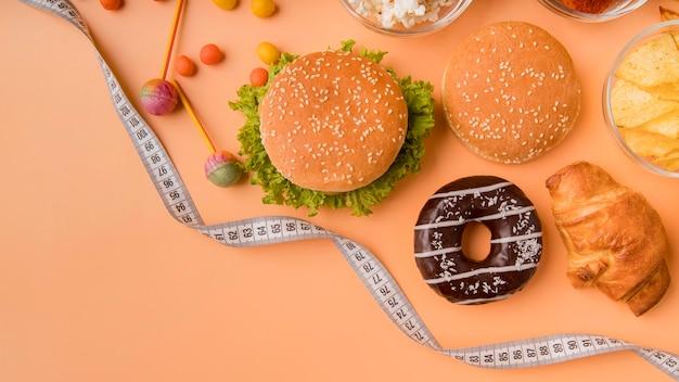 Vista superior de hamburguesas y aperitivos con cinta métrica