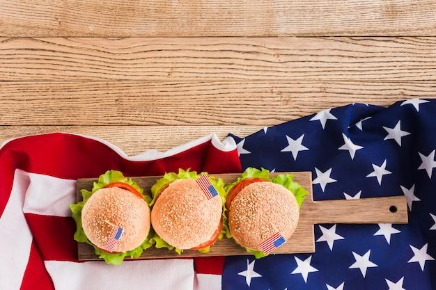 Vista superior de hamburguesas con bandera americana en superficie de madera