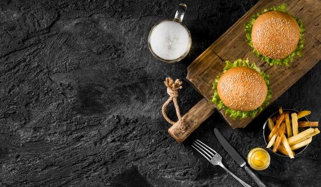 Vista superior de hamburguesas y papas fritas con cerveza y espacio de copia
