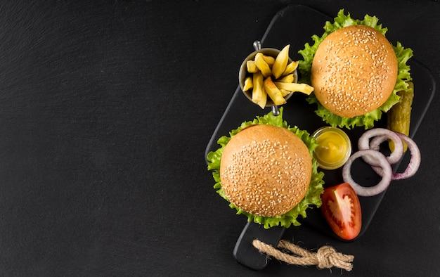 Vista superior de hamburguesas y papas fritas con encurtidos y espacio de copia