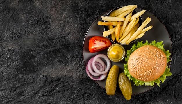 Vista superior de hamburguesas y papas fritas en un plato con encurtidos y espacio de copia