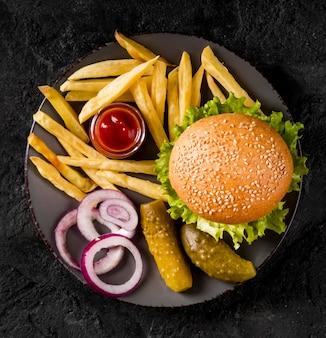 Vista superior de hamburguesas y papas fritas en un plato con encurtidos