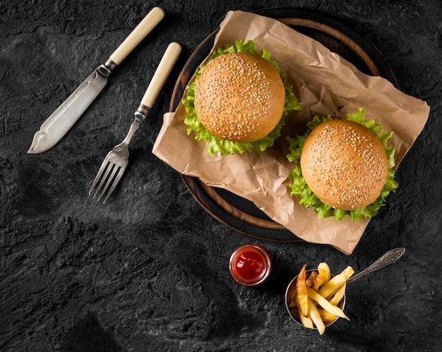 Vista superior de hamburguesas y papas fritas con salsa