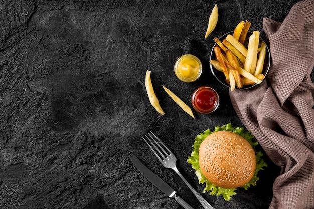 Vista superior de hamburguesas y papas fritas con salsas y espacio de copia