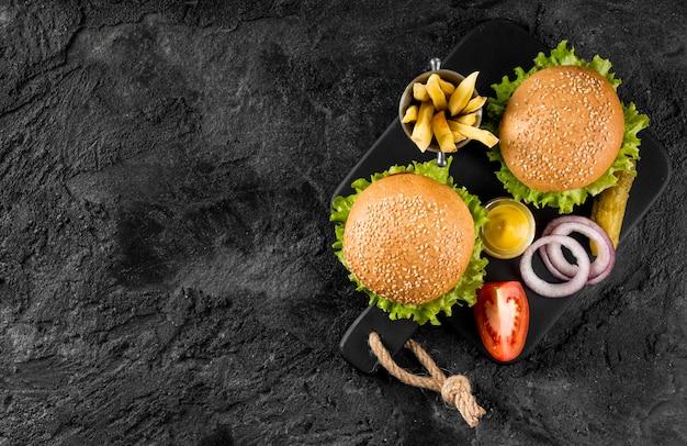 Vista superior de hamburguesas y papas fritas en tabla de cortar con pepinillos y espacio de copia