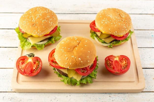 Una vista superior de hamburguesas de pollo con queso y ensalada verde en el escritorio de madera
