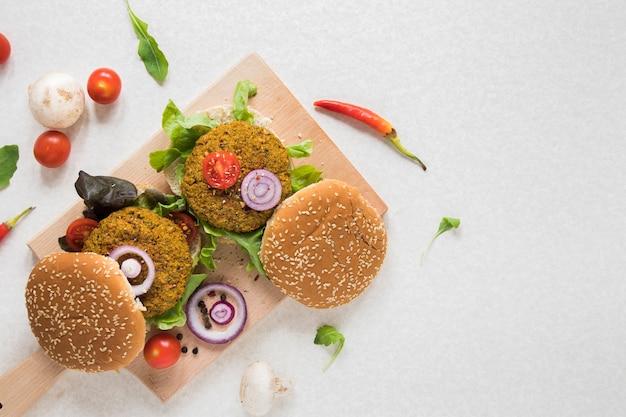Vista superior hamburguesas veganas sobre tabla de madera con espacio de copia