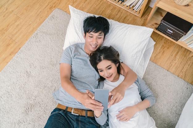 Vista superior de happy asian lover utilizando el teléfono inteligente de tecnología para selfie en el piso