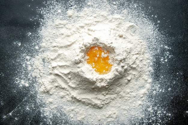 Vista superior de harina blanca mezclada con huevo en el fondo oscuro trabajo de pastelería pastel de huevo pastel de panadería trabajador cocina