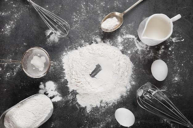 Vista superior de harina con herramientas para hornear sobre la mesa