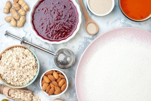 Vista superior de harina en polvo en cuencos de placa con semillas de sésamo, avena, almendras, mermelada, cacahuetes, cuchara de madera en la mesa