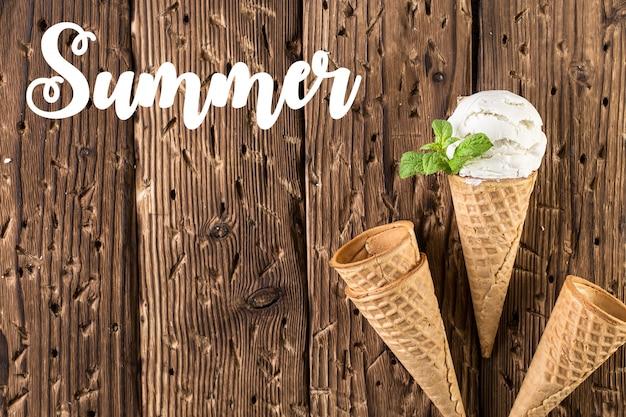 Vista superior de helado blanco en cono de waffle sobre fondo rústico