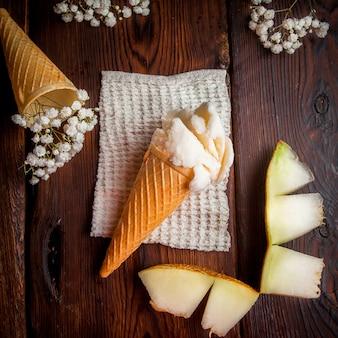 Vista superior de helado en un cono de waffle con rodajas de melón y gypsophila en servilletas de trapo