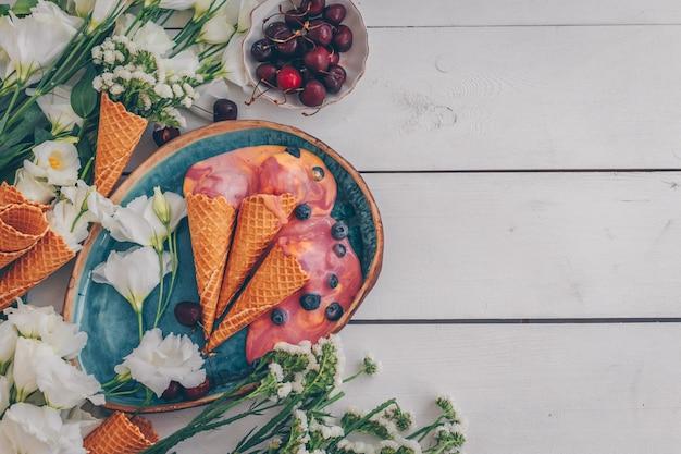 Vista superior helado en plato azul con flores y frutas en madera blanca