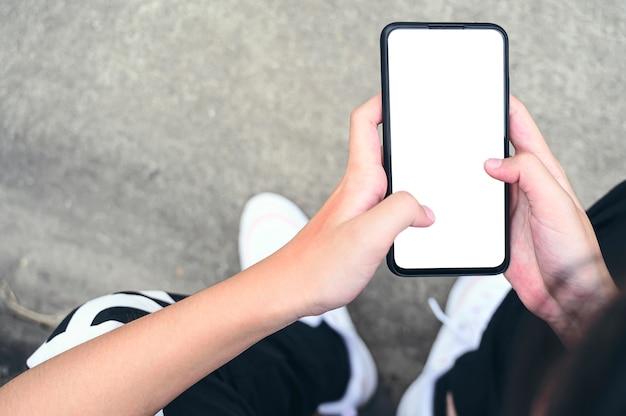 Vista superior de la hembra joven con smartphone, pantalla en blanco para texto o diseño gráfico.